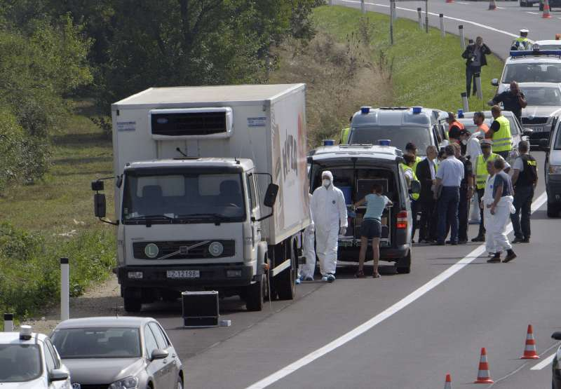Investigators are seen around the truck in which dozens of dead bodies were found at the side of the highway to Vienna near Parndorf, Austria, on Aug. 27, 2015. A truck with Hungarian license plates parked at the side of the highway to Vienna early Thursday morning was discovered to have dozens of dead bodies inside, Austrian police said on Thursday.