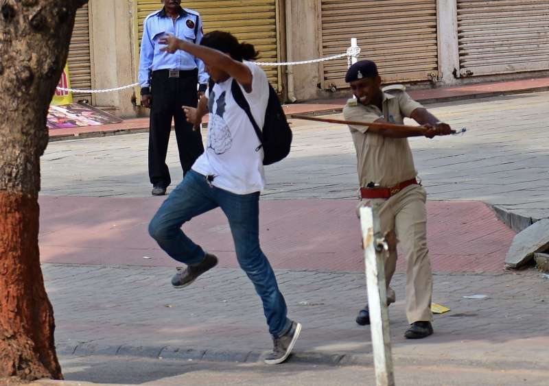 A Gujarat policeman beats  journalist covering the Patel protest at Ahmedabad