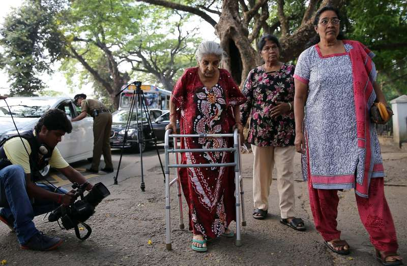 A senior citizen (C) arrives at a polling center in Colombo