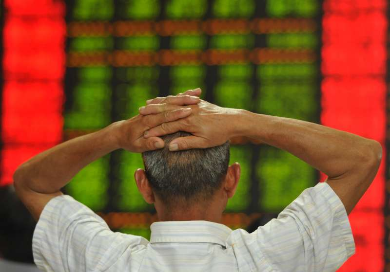 An investor follows information at a stock trading hall in Fuyang, east China's Anhui Province, July 15, 2015. Chinese shares fell back into negative territory on Wednesday despite better-than-expected second-quarter economic growth. The benchmark Shanghai Composite Index slumped 3.03 percent to close at 3,805.7 points. The smaller Shenzhen Component Index dived 4.68 percent to close at 12,132.42 points