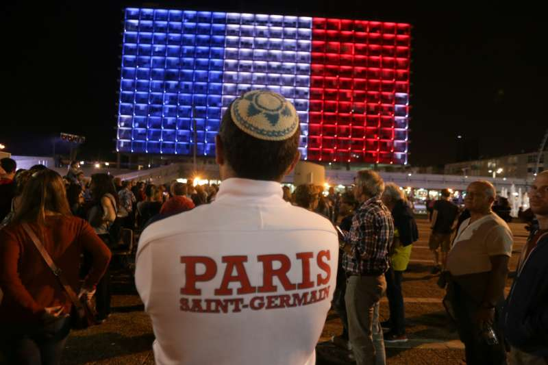 People attend a gathering to mourn for the victims of the Paris attacks in front of the Tel Aviv city hall, which is lit with the colors of the French national flag, at Rabin Square in Tel Aviv, Israel,