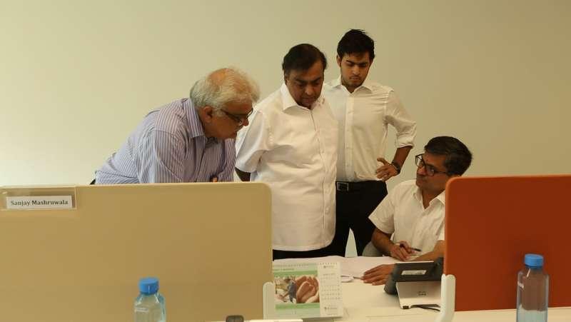 Mukesh Ambani, standing centre, with son Akash Ambani, at his left, confidant Manoj Modi, seated, and human resource head Sanjay Jog, at the Reliance Jio open office
