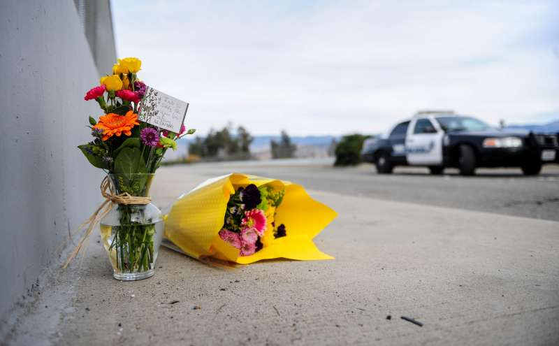Flowers are left by the side of the road as police blocks the road leading to the site of the mass shooting in San Bernardino, California, Dec. 3, 2015. Police continue to investigate a mass shooting at the Inland Regional Center in San Bernardino that left at least 14 people dead and another 21 injured.