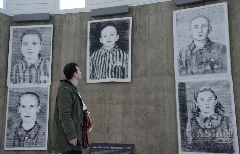 """A visitor looks at Austrian artist Manfred Bockelmann's exhibition """"Drawing Against Oblivion"""" in Zagreb, capital of Croatia, Jan. 26, 2016. The exhibition of works by Austrian painter Manfred Bockelmann, displaying portraits of the 60 children killed in Nazi death camps, mostly Auschwitzby, will be opened on International Holocaust Remembrance Day"""