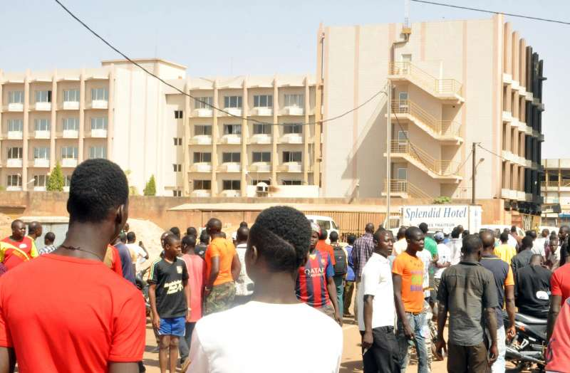 People gather outside the Splendid Hotel in Burkina Faso's capital Ouagadougou, Jan. 16, 2015. Twenty-three people have been killed and many others wounded after the Al-Qaida in the Islamic Maghreb (AQIM) attacked the Splendid Hotel and took hostages there Friday. Security forces have freed 126 hostages and killed four attackers on Saturday
