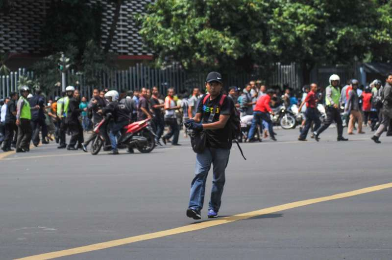 Photo taken on Jan. 14, 2015 shows a suspect terrorist with a gun at Thamrin street in Jakarta, Indonesia. At least six explosions were heard in the shopping mall of Sarinah located at the heart of Indonesian capital on Thursday morning, with fire exchange between a terrorist group and police occurring around the mall premises.