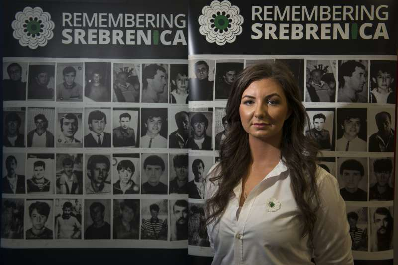 Student Amra Mujkanović, 21, has joined the Scotland board of Remembering Srebrenica and is pictured with images of victims of the Srebrenica genocide