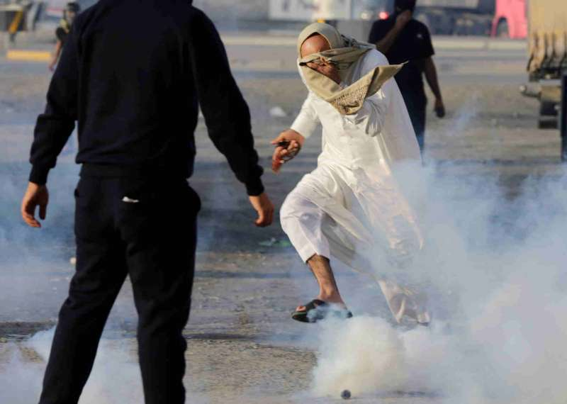 A protester runs away from tear gas fired by riot police during clashes at an anti-government demonstration in the village of Sitra, south of Manama, Bahrain