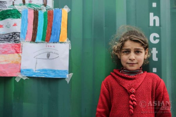 A refugee girl poses in front of colorful drawings at the Kara Tepe hotspot on Lesvos island . The camp which is run by the local municipality remains an open facility with a total of 500 migrants and refugees registered before the EU-Turkey deal to stem the refugee influx came into effect on March 20