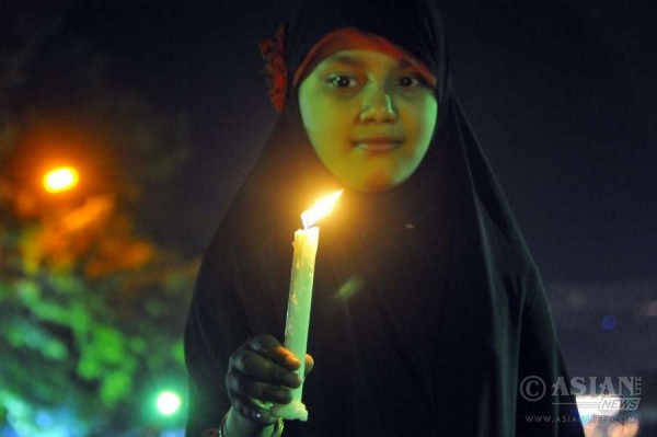A Bangladeshi girl holds a candle during a celebration to mark the forthcoming Independence Day and National Day in Dhaka, Bangladesh