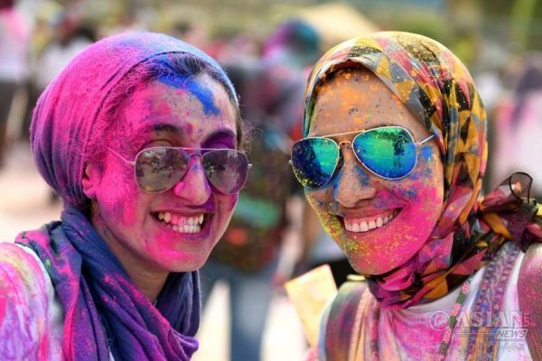 People participate in the India Color Festival amid colored powder in Giza, Egypt
