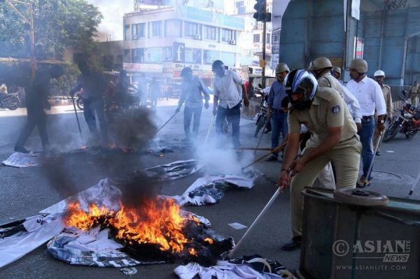 "Surat: A policeman tries to douse fire lit by the members of Patidar Anamat Andolan Samiti (PAAS) during ""Jail Bharo Andolan"" in Surat of Gujarat"
