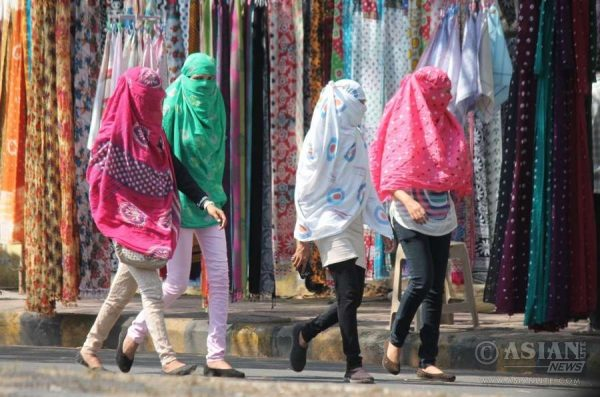 Women cover their faces to avoid direct contact with sun on a hot day