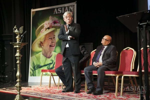 British Speaker John Bercow addressing the Indian community in the shadow of a huge poster of Asian Lite cover page on the Queen. Mr Buddhdev Pandya MBE, Political Editor, Asian Lite, is also seen