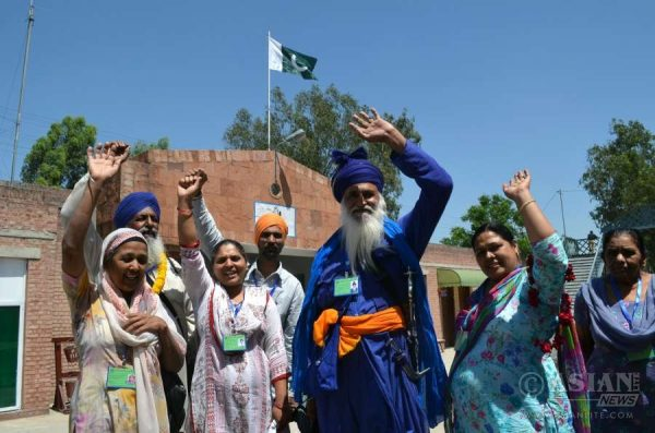 Indian Sikh pilgrims wave as they arrive at the Wagah railway station in Lahore, eastern Pakistan, April 12, 2016. About 460 Indian Sikh pilgrims arrived in Pakistan for Baisakhi's celebrations, the Sikh New Year, at the Sikh Shrine of Gurudwara Panja Sahib and Nankana Sahib, the birthplace of Sikh faith founder Guru Nanak Dev.