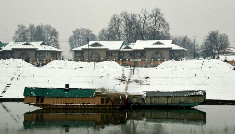 Srinagar: A view of houseboats on Jhelum river after snowfalls in Srinagar. (Photo: IANS) by .