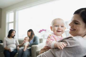 Mother holding smiling baby in living room by .