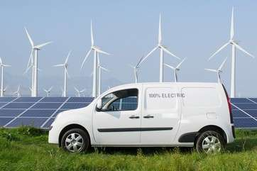 Electric van in front of solar panels and wind turbines by .