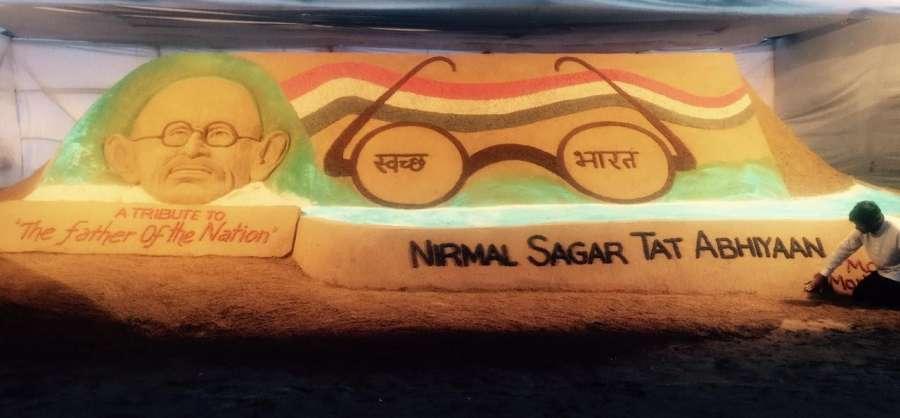 Mumbai: Renowned sand artist Sudarsan Pattnaik pays tribute to Father of Nation Mahatma Gandhi on the eve of the second anniversary of Swachch Bharat Abhiyan and Gandhi Jayanti at Mumbai Chowpatty on Oct 1, 2016. (Photo: IANS) by .