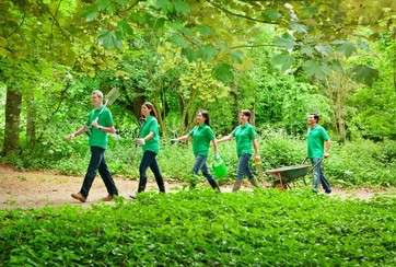 Gardeners carrying tools in park by .