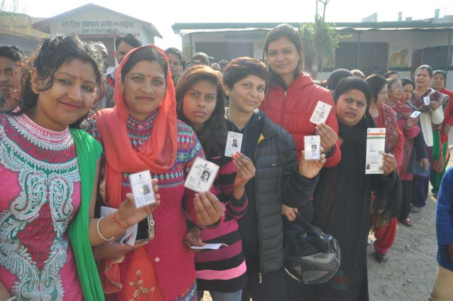 Dehradun: People stand in a queue to cast their vote for Uttarakhand assembly elections in Dehradun on Feb. 15, 2017. (Photo: IANS) by .