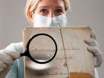 Woman with magnifying glass showing file by .