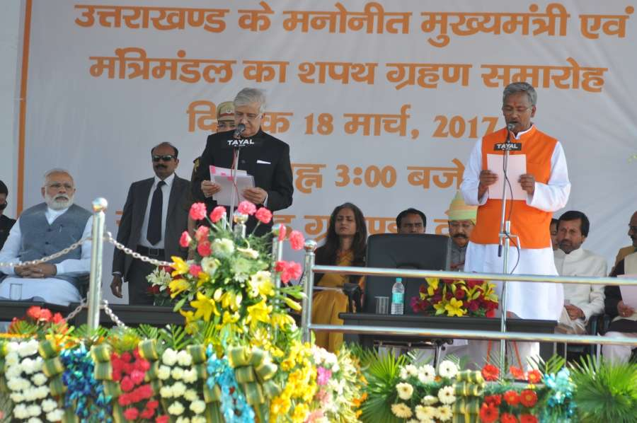 Dehradun: Uttarakhand Governor Krishan Kant Paul administer the oath to Trivendra Singh Rawat as Chief Minister of Uttarakhand during a swearing in ceremony in Dehradun, on March 18, 2017. Also seen Prime Minister Narendra Modi. (Photo: IANS) by .