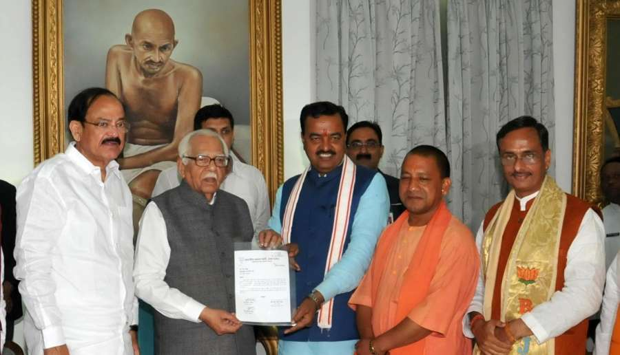 Lucknow: BJP's Uttar Pradesh Chief Minister designate Yogi Adityanath with Deputy Chief Ministers designate Keshav Prasad Maurya and Dinesh Sharma (R) meets Uttar Pradesh Governor Ram Naik, stakes claim to form the government, in Lucknow on March 17, 2017. Also seen Union Minister For Urban Development And Poverty Alleviation M Venkaiah Naidu. (Photo: IANS) by .