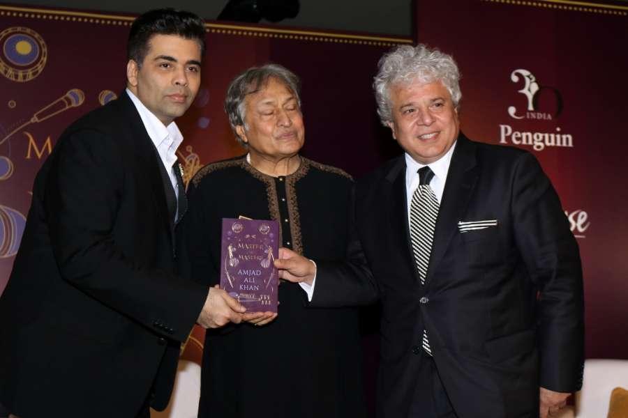 Mumbai: Filmmaker Karan Johar, sarod maestro Ustad Amjad Ali Khan and author Suhel Seth during the launch of his book Master on Masters in Mumbai on March 28, 2017. (Photo: IANS) by .
