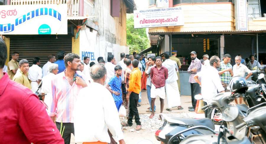 Kannur: People queue up outside a Kerala State Beverages (M&M) Corporation Ltd outlet in Kannur to buy liquor after the Supreme Court banned liquor shops within 500 metres on either side of the national and state highways in a bid to curb accidents caused by drunken driving; on April 3, 2017. (Photo: IANS) by .