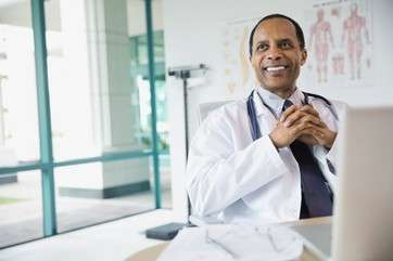 Portrait of confident male doctor smiling by .