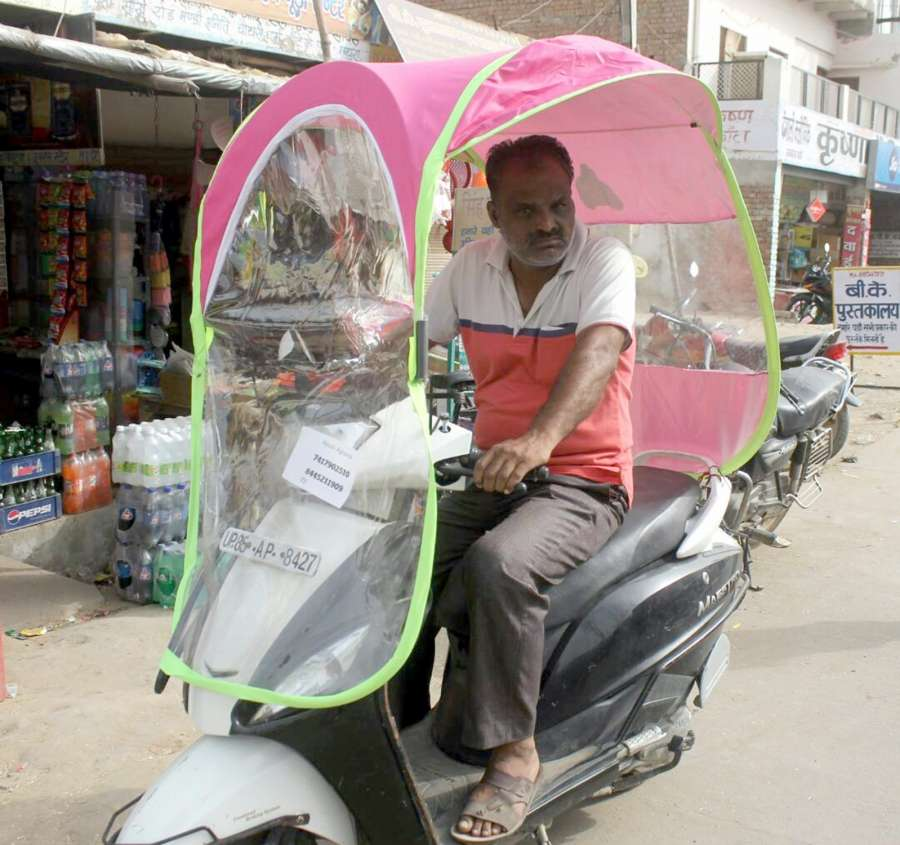 Mathura: A man riding a two-wheeler fitted with an umbrella to beat the scorching heat in Mathura on April 22, 2017. (Photo: IANS) by .