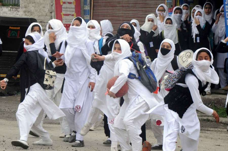 Srinagar: Girls pelt stones on security personnel during a protest in Srinagar. (Photo: IANS) by .