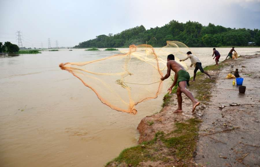 Kamrup: Fishermen cast their nets in the Brahmaputra river in Kamrup district of Assam on June 16, 2017. (Photo: IANS) by .
