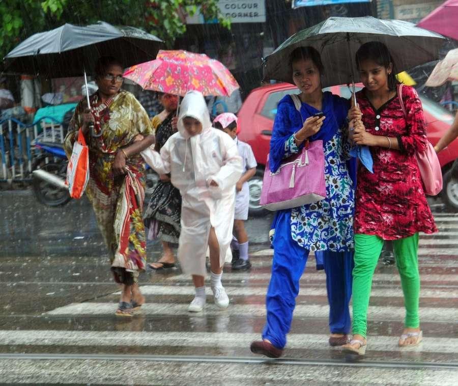 Kolkata: People use umbrellas to protect themselves from rains in Kolkata on June 24, 2017. (Photo: Kuntal Chakrabarty/IANS) by .