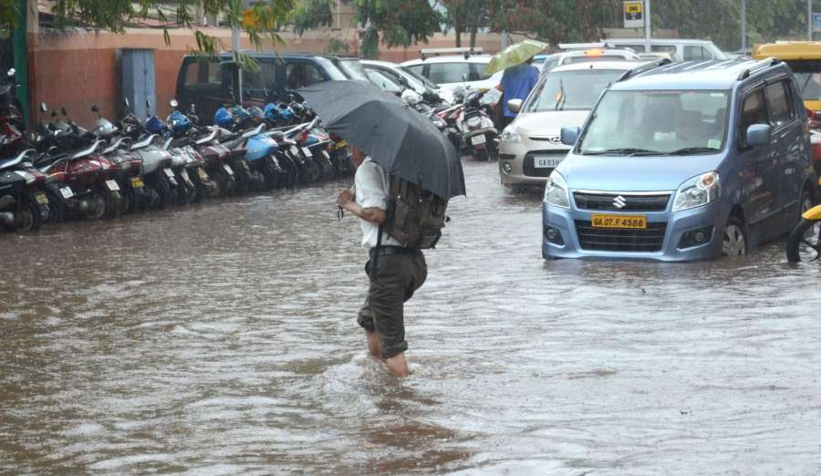 Panaji: A man wades through water logged streets of Panaji after pre monsoon showers lashed the city on May 31, 2017. (Photo: IANS) by .