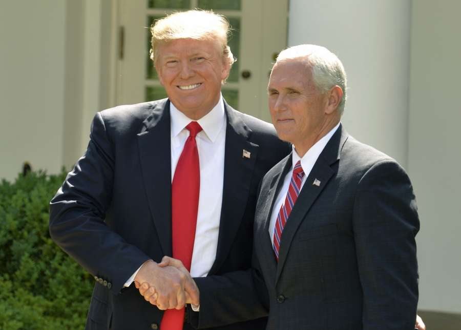 WASHINGTON, June 1, 2017 (Xinhua) -- U.S. President Donald Trump (L) shakes hands with U.S. Vice President Mike Pence before delivering a speech at the White House in Washington D.C., capital of the United States, on June 1, 2017. U.S. President Donald Trump said on Thursday that he has decided to pull the United States out of the Paris Agreement, a landmark global pact to fight climate change. (Xinhua/Mike Theiler/IANS) by .