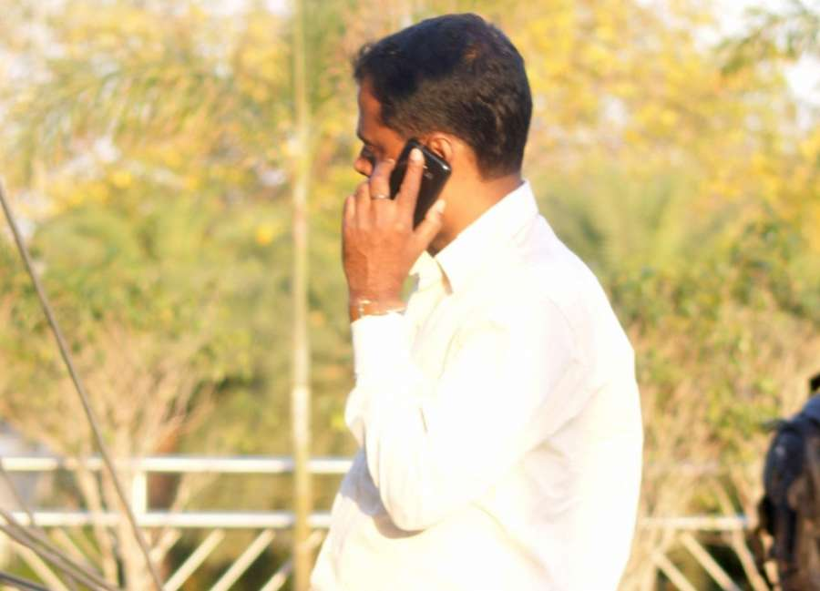 A man busy talking over his mobile phone. (File Photo: IANS) by .