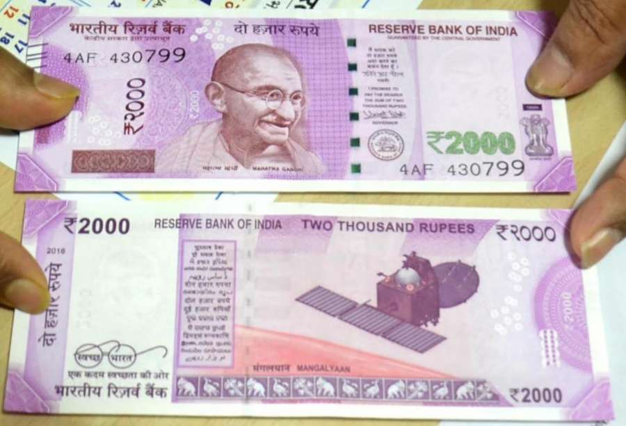 Ranchi: A Bank employee shows Rs 2000 rupee currency notes at the State Bank of India branch in Ranchi on Nov. 10, 2016. (Photo: IANS) by .