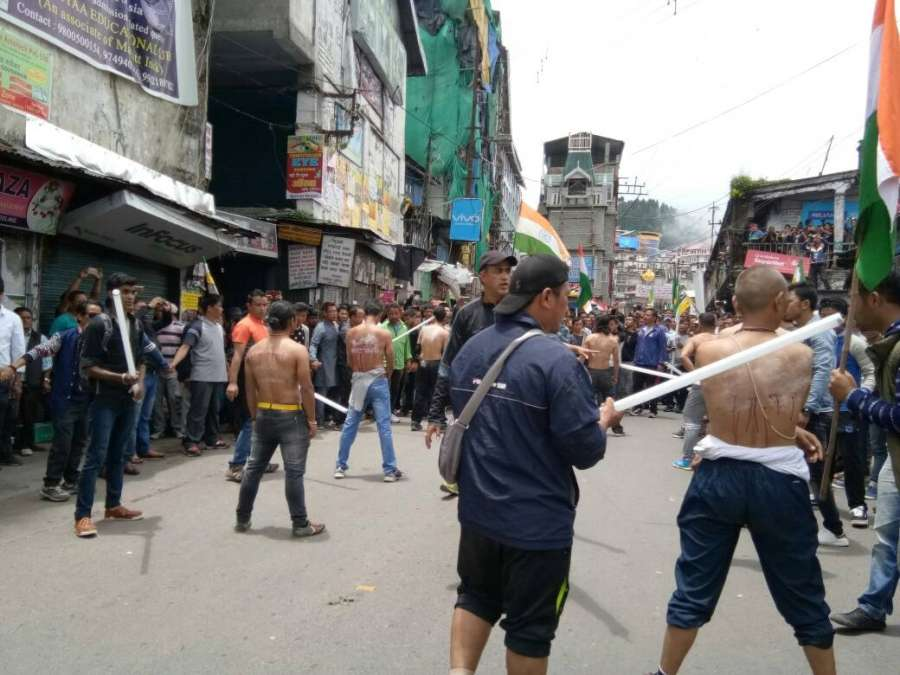 "Darjeeling: Activists of the Yuva Morcha - the youth wing of the GJM a ""tubelight rally"" and broke the tubelight rods on their back to protest against state government and police action in Darjeeling on June 27, 2017. (Photo: IANS) by ."