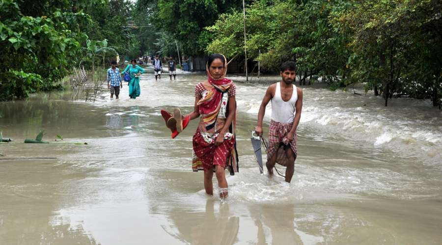 Morigaon: People wade through flooded Morigaon district of Assam on Aug 14, 2017. (Photo: IANS) by .