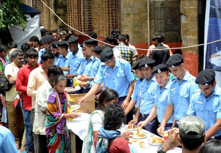 Mumbai: Navy personnel serve food to people at a canteen opened by the Navy to provide relief to commuters stranded due to heavy rains at the Chhatrapati Shivaji Terminus (CST) Railway station in Mumbai on Aug 30, 2017. (Photo: Sandeep Mahankal/IANS) by .