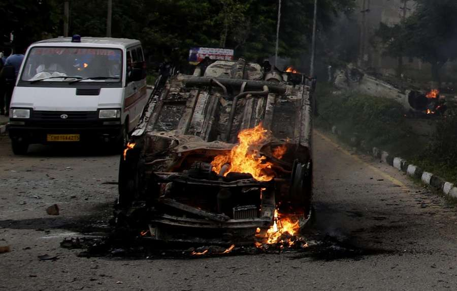 Panchkula: A vehicle set on fire by protesters in Panchkula after the conviction of Dera Sacha Sauda sect chief Gurmeet Ram Rahim Singh in a rape case on Aug 25, 2017. At least 12 people were killed in firing by security forces as enraged supporters of Dera Sacha Sauda chief Gurmit Ram Rahim Singh went on a rampage. (Photo: IANS) by .