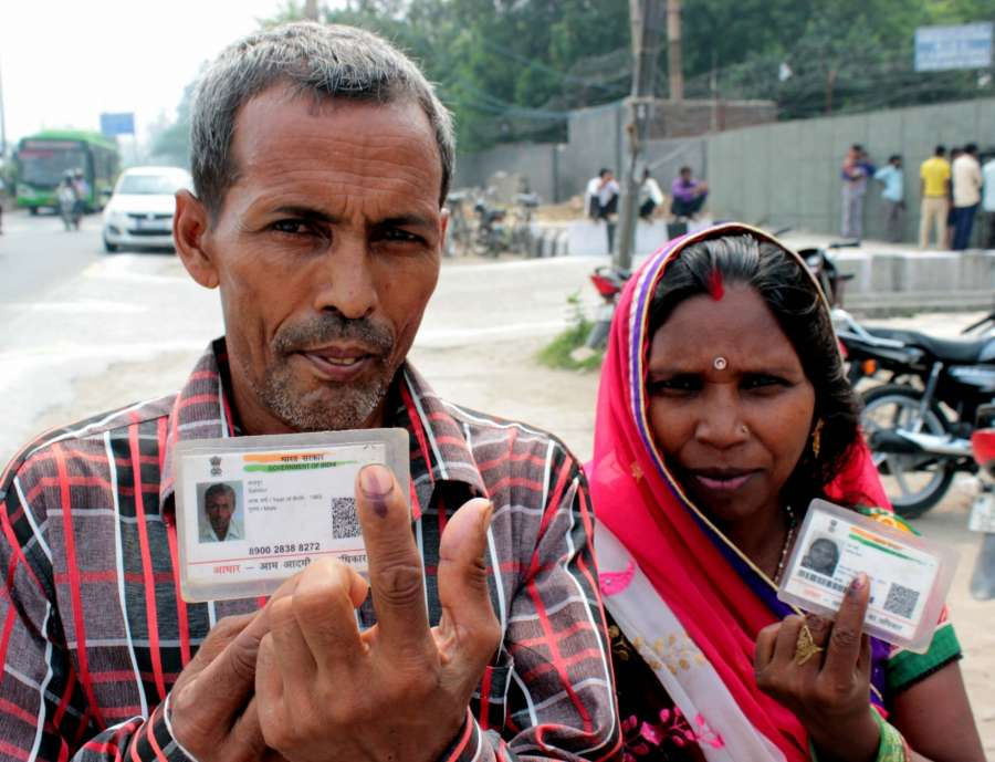 New Delhi: People show their fingers marked with phosphorus ink along with their Aadhar cards after casting their votes for the Bawana assembly constituency bypolls in New Delhi on Aug 23, 2017. (Photo: IANS) by .