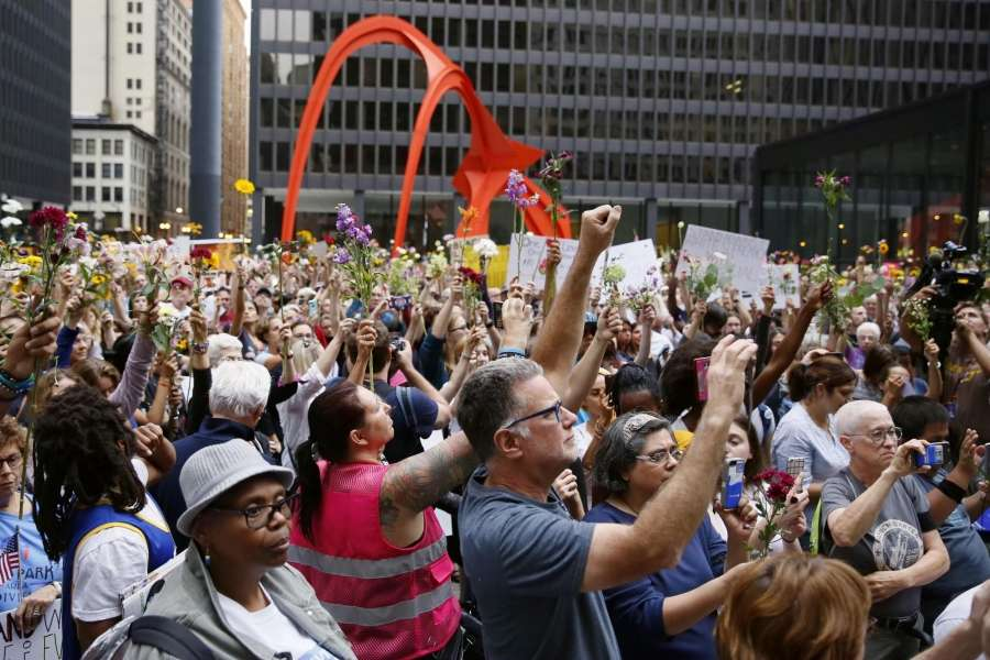 CHICAGO, Aug. 14, 2017 (Xinhua) -- People raise flowers during an evening vigil at Federal Plaza in Chicago, the United States, on Aug. 13, 2017. Several hundred people joined a Sunday evening vigil at Federal Plaza in downtown Chicago, for those who fell victim to the violence in Charlottesville of Virginia during the weekend.(Xinhua/Wang Ping/IANS) by .