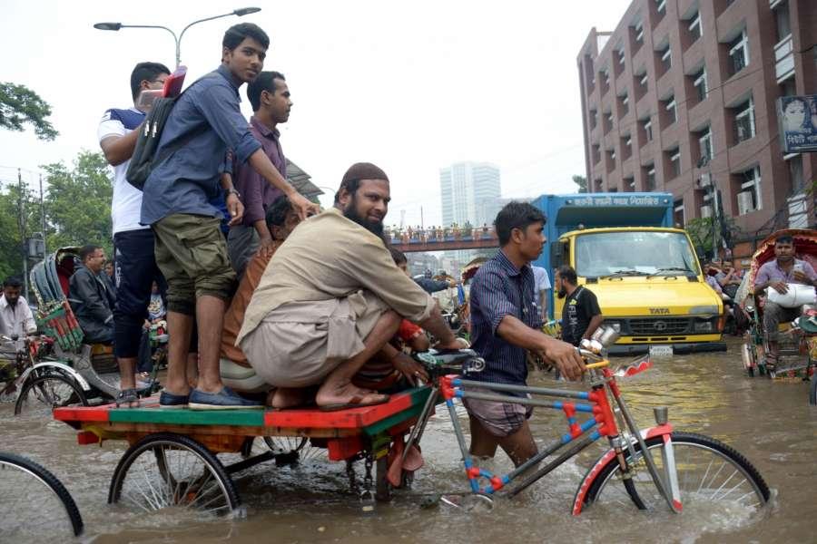 DHAKA, July 26, 2017 (Xinhua) -- People wade through a water-logged road after heavy rains in Dhaka, Bangladesh, July 26, 2017. (Xinhua/Salim Reza/IANS) by .