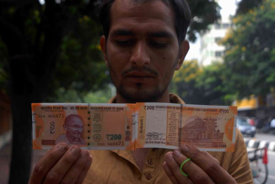 Hyderabad: A man shows the new Rs 200 currency note outside Reserve Bank of India in Hyderabad on Aug 29, 2017. (Photo: IANS) by .