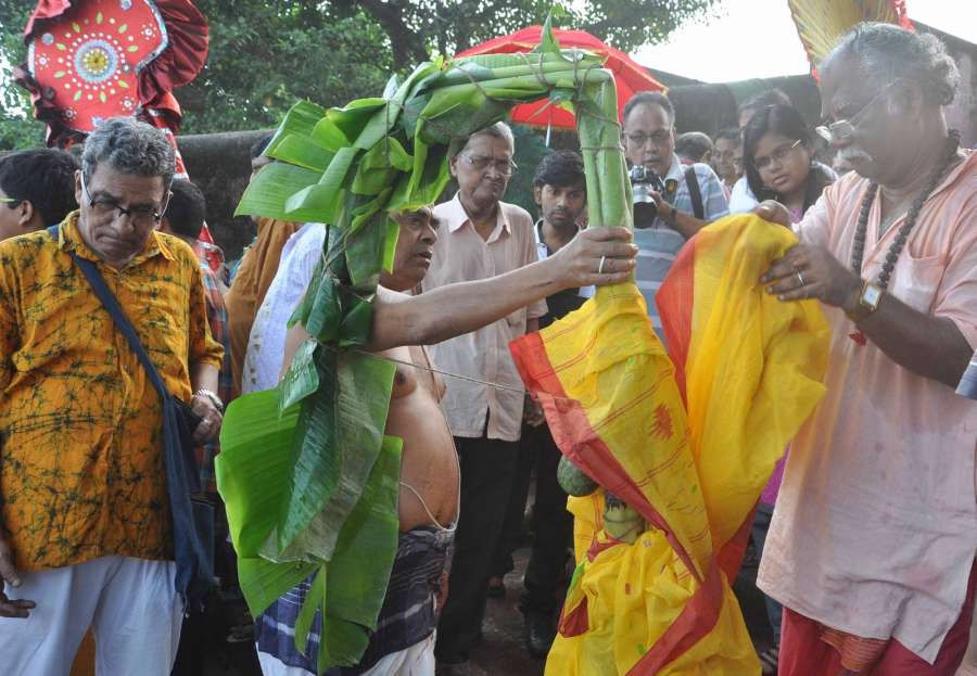 Kolkata: Devotees perform rituals with a banana tree wrapped in a sari, during 'Nabapatrika snan' or 'Kolabou snan' (bathing of banana bride) at the Ganga river during the Durga Puja in Kolkata on Sept 27, 2017. The stem of a banana plant is bathed and draped in a red and white saree that make it look like a newly wed bride and then placed beside Lord Ganesha as 'Kalabou' is considered to be his wife according to Hindu mythology. (Photo: Kuntal Chakrabarty/IANS) by .