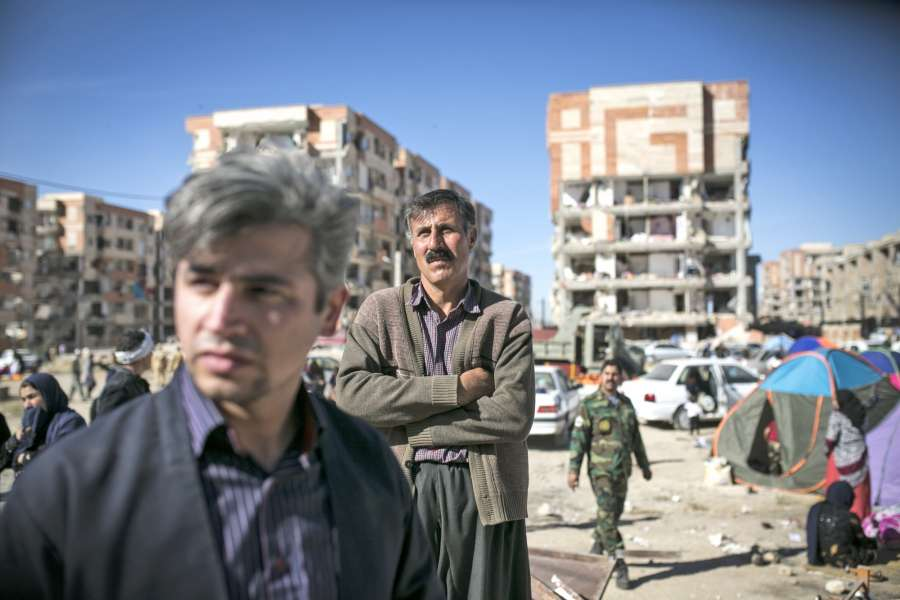 SARPOL-E ZAHAB, Nov. 13, 2017 (Xinhua) -- People stand in front of damaged buildings in Sarpol-e Zahab, Iran, Nov. 13, 2017. The powerful 7.3-magnitude earthquake which hit the border region between Iran and Iraq on Sunday has killed at least 395 Iranians, state TV reported on Monday. (Xinhua/Ahmad Halabisaz/IANS) by .