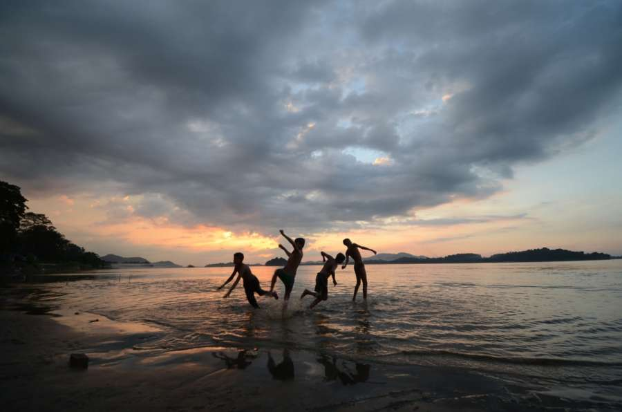 Guwahati: Children enjoy themselves on the banks of Brahmaputra river at dusk in Guwahati, on Oct 12, 2017. (Photo: IANS) by .